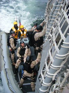 VBSS (Visit, Board, Search and Seizure) anti-piracy team training; Katie is driving boat; VBSS team transitions down sea ladder while ship is underway