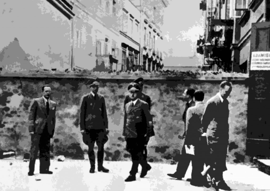 Members of the Nazi occupation authorities gather outside a wall dividing the ghetto from the rest of Warsaw