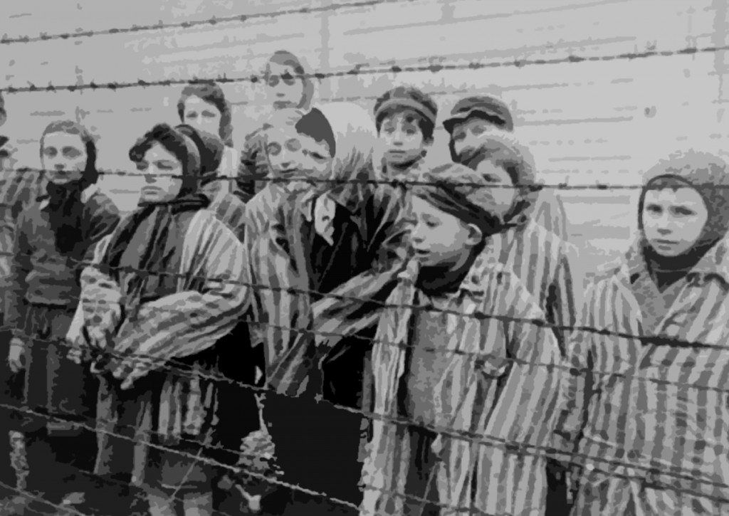 Jewish children, kept alive in the Auschwitz II (Birkenau) concentration camp, pose in concentration camp uniforms between two rows of barbed wire fencing after liberation