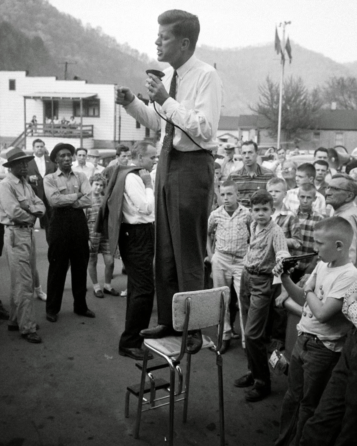 John F. Kennedy campaigns in rural West Virginia, precariously perched on a high-chair to deliver his speech. 1960
