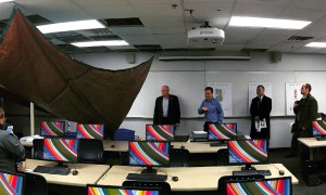 Tarp protecting computers from roof-water leakage in Business building classroom
