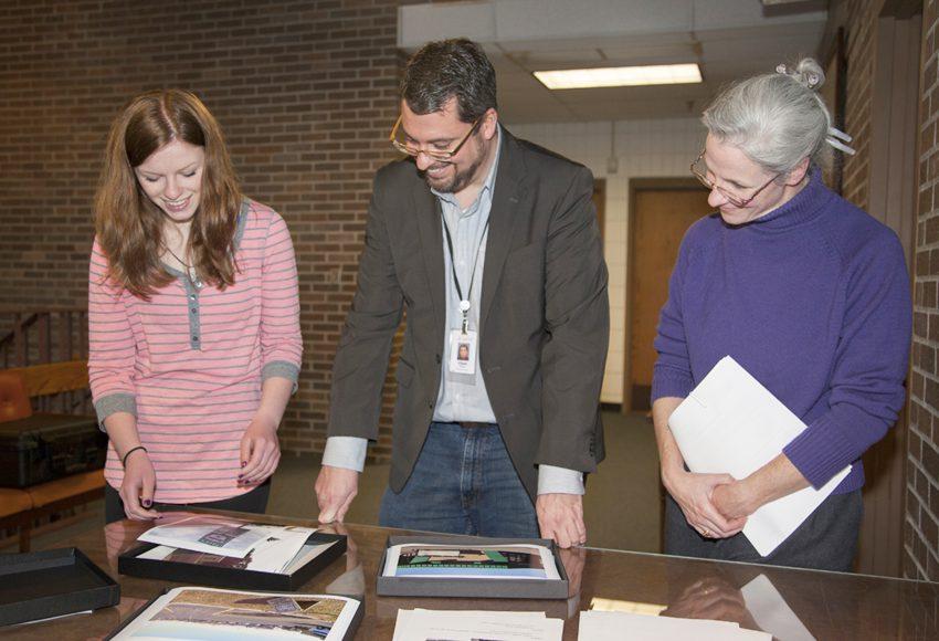 LCOM student handing off Robert Street photos to Dakota County Historical Society director